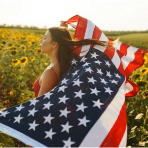Girl in flower fields with American flag blowing in the wind